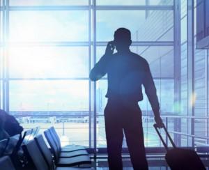 Geschftsreisender mit Koffer telefoniert im Flughafen