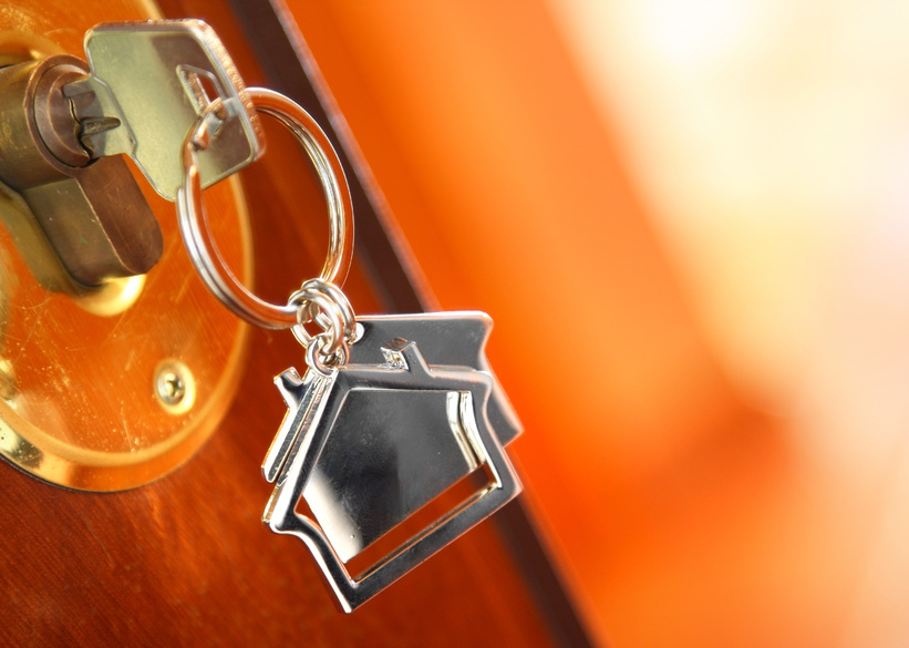 key in a lock with a house-shaped keyring