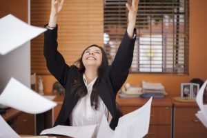 Happy businesswoman tossing papers in the air