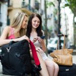 Two female friends with luggage using the map at smartphone