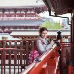 Caucasian woman a tourist walking with camera in Japanese shrine temple, Japan