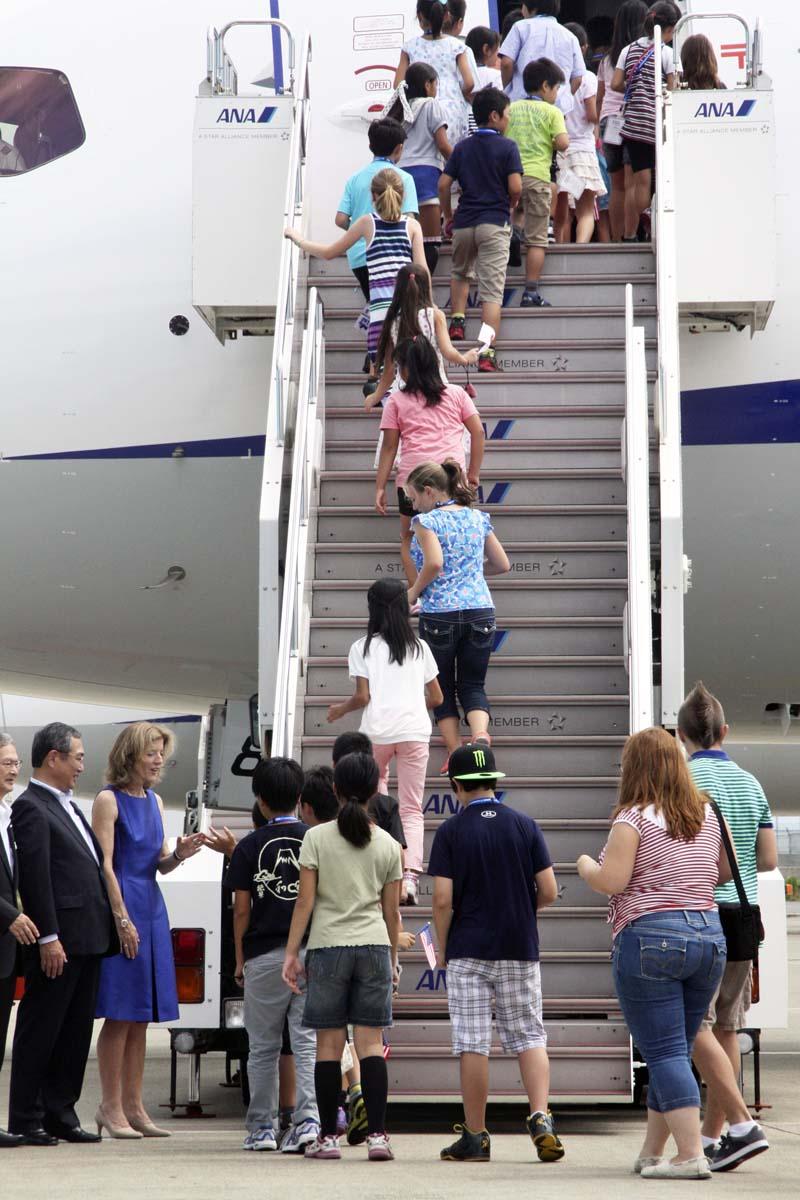 ケネディ大使とANAの伊東信一郎会長らに見送られて乗り込む子供たち