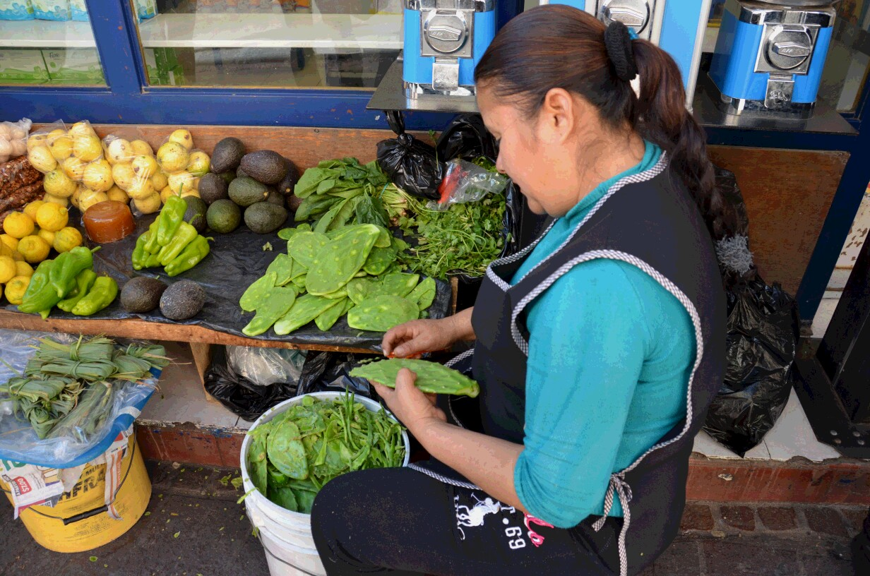 ウチワサボテンはメキシコの代表的な野菜。店先でトゲを取っている女性