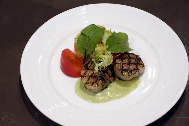 成田発洋食メニューの一例「ホタテのグリル」。クスクスサラダが添えられ、わさびソースでいただく