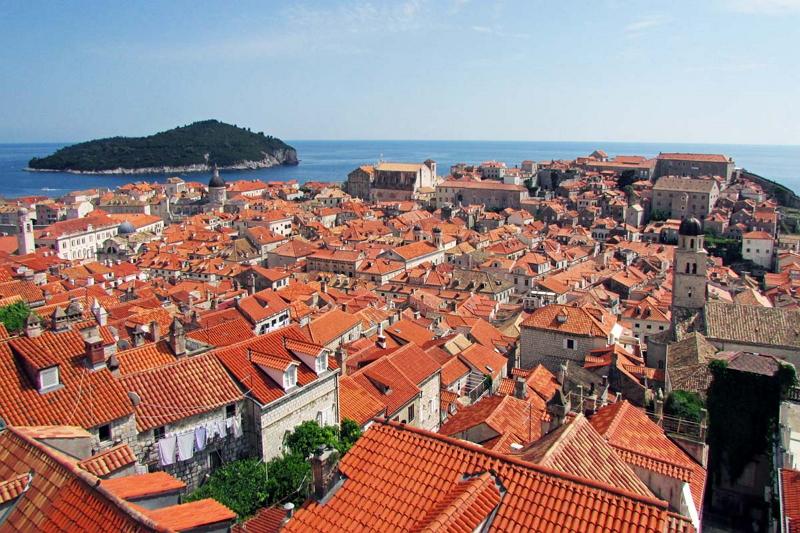青い海と中世の城壁に囲まれたドゥブロヴニクの美しい街並み。オレンジ色のレンガ屋根が連なる