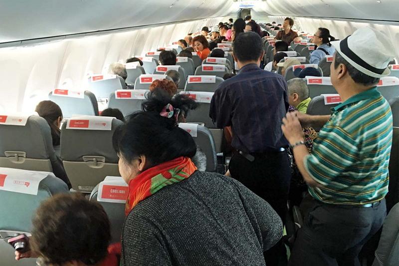 日本観光の最後の思い出にと、機窓からの富士山の絶景を目に焼き付ける中国人旅行者たち