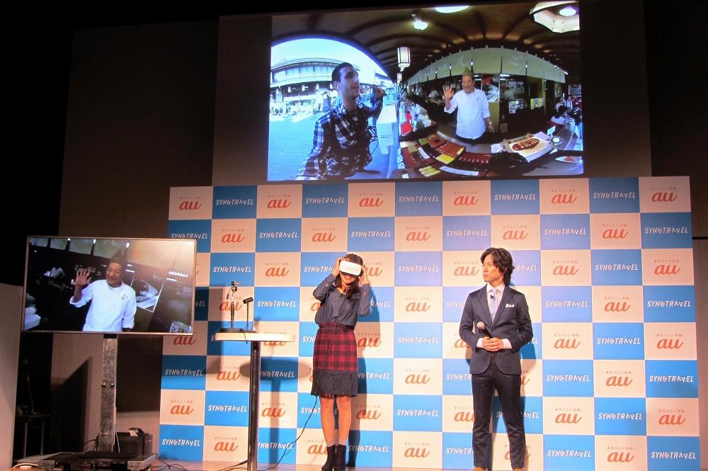 記者会見では、会場と柴又をVR画像で中継し、SYNC TRAVELの疑似体験も実施。左の小さい画面はモデルの女性が見ている映像、上部の映像は現地の様子で、モデルと柴又の団子やの主人がガイドのカメラとマイクを通じて会話している